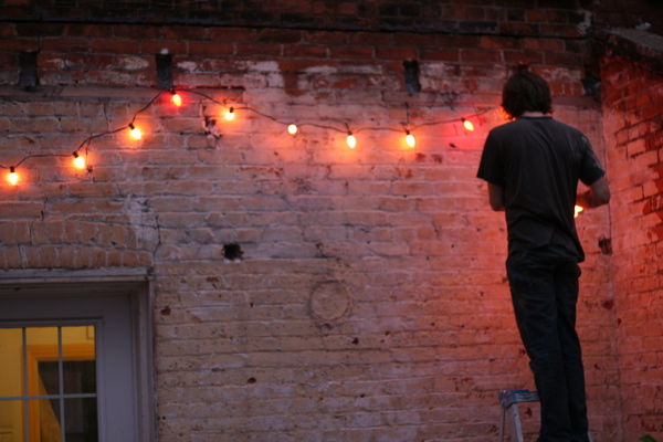 Hanging up Christmas lights in July, backyard lights